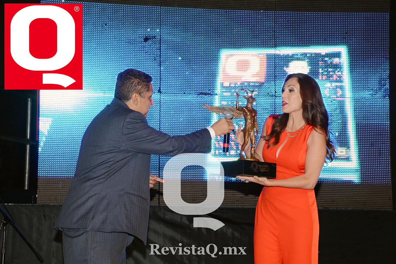 El editor de Q entregando el  micrófono a Nora  Salinas para que ofrezca unas palabras en los Premios Q